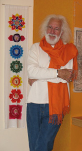 Doug von Koss in orange scarf stands beside a yoga alter.
